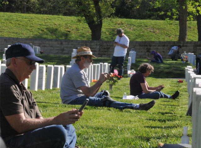Installation Management Command and Fort Riley Directorate of Public Works employees work together taking photographs of headstones May 14 at the Fort Riley Cemetery. (photo courtesy Fort Riley)
