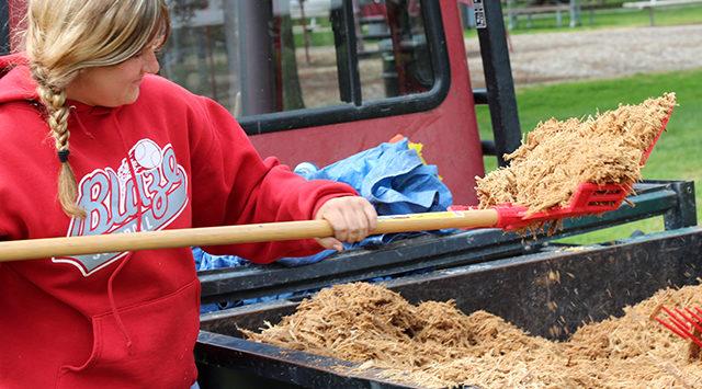 Amber Bird with the city of Salina shovels mulch.
