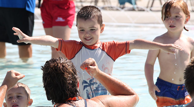 """Mason stretches out his arms in the """"wing"""" position before learning how to float in the water"""