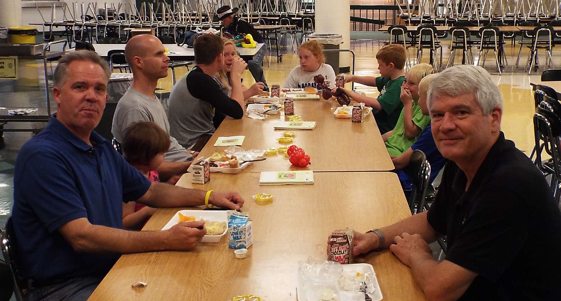 Salina Mayor Jon Blanchard (left) and city commissioner Randall Hardy (right) eat lunch with the children