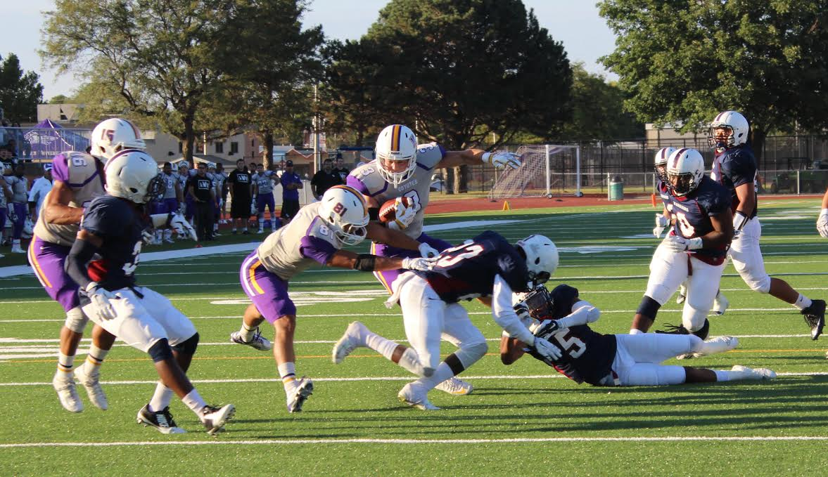 KWU Sophomore Miles Balthazor makes a carry while Senior Joe Vela, WR, blocks. (Photo Courtesy of Dr. David S. Silverman, Associate Professor of Communication Studies and Theatre Arts, Kansas Wesleyan University)