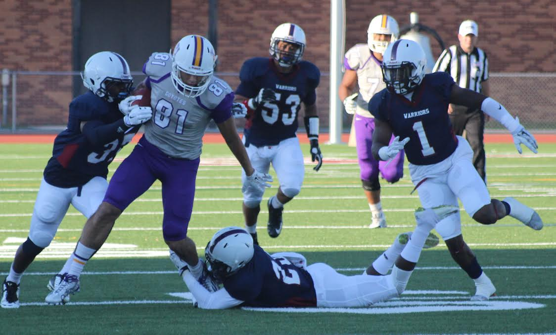 Senior Joe Vela, WR, fends off two defenders for extra yards in the first half. (Photo Courtesy of Dr. David S. Silverman, Associate Professor of Communication Studies and Theatre Arts, Kansas Wesleyan University)