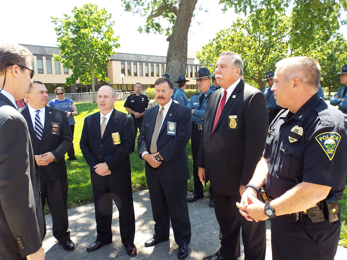 Governor Brownback (far left) talks with several law enforcement officers, including Salina Police Chief Brad Nelson (far right).