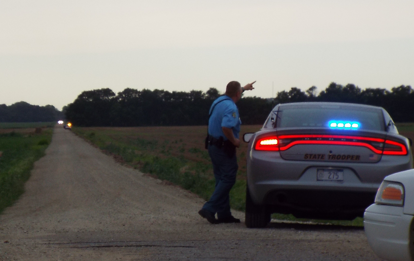 Saline County Sheriff Investigator Matt Fischer briefs a state trooper on the situation as the trooper arrives.