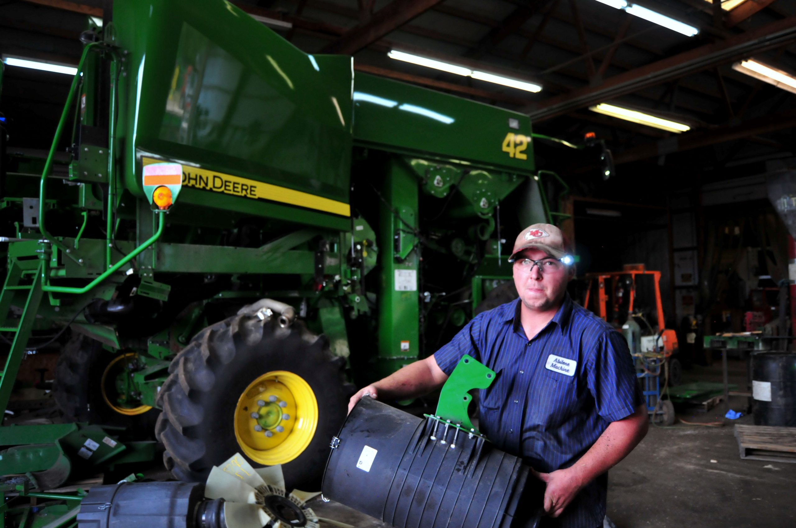Alex Shewmon, Combine Parts Technician at Abilene Machine, takes good used parts from a damaged John Deere Combine at one of the shops at the company's facility near Solomon, Kansas, Sept. 2, 2020. Abilene Machine started in 1980 as an agricultural machinery salvage parts and equipment resale operation. (Photo by Torey Griffith, Digital Marketing Specialist at Abilene Machine)